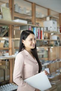 オフィスでパソコンを抱えて立っている女性の写真素材 [FYI04315591]