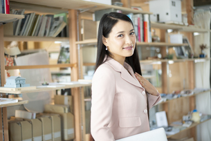 オフィスでパソコンを抱えて立っている女性の写真素材 [FYI04315592]