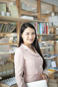 オフィスでパソコンを抱えて立っている女性の写真素材 [FYI04315595]