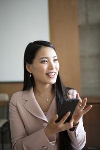 オフィスでスマホを持って笑っている女性の写真素材 [FYI04315599]