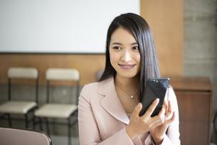 オフィスでスマホを持って笑っている女性の写真素材 [FYI04315601]