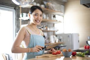 キッチンで料理をしている笑顔の女性の写真素材 [FYI04315610]