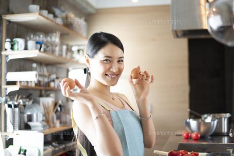 キッチンで卵を持って笑っている女性の写真素材 [FYI04315611]