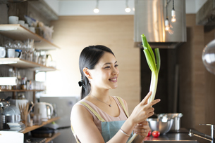キッチンでネギを持って笑っている女性の写真素材 [FYI04315612]