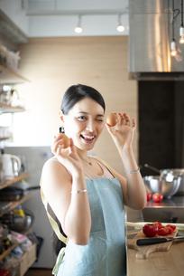 キッチンで卵を持って笑っている女性の写真素材 [FYI04315613]