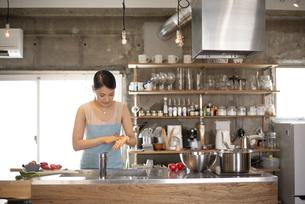 キッチンで料理をしている女性の写真素材 [FYI04315615]