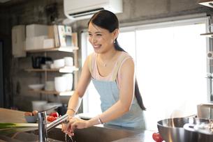 キッチンで料理をしている女性の写真素材 [FYI04315616]