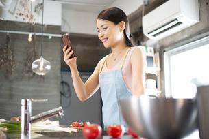 キッチンでスマホを見ている女性の写真素材 [FYI04315617]