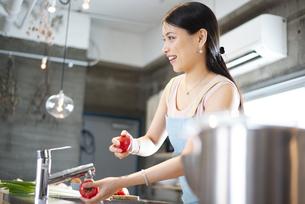キッチンでトマトを洗っている女性の写真素材 [FYI04315618]
