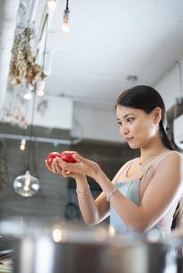 キッチンでトマトを持っている女性の写真素材 [FYI04315619]