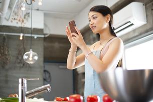 キッチンでスマホを見ている女性の写真素材 [FYI04315620]