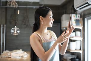キッチンでスマホを見ている女性の写真素材 [FYI04315621]