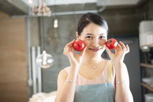 キッチンでトマトを持っている女性の写真素材 [FYI04315622]