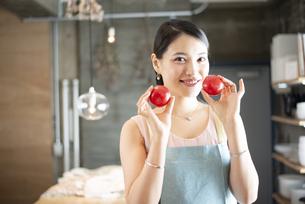キッチンでトマトを持っている女性の写真素材 [FYI04315623]