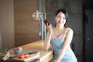 キッチンでスマホを持っている女性の写真素材 [FYI04315627]