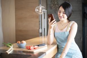 キッチンでスマホを見ている女性の写真素材 [FYI04315628]