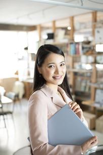 オフィスでファイルを持っている笑顔の女性の写真素材 [FYI04315634]