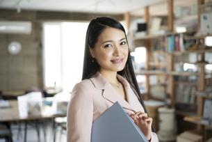 オフィスでファイルを持っている笑顔の女性の写真素材 [FYI04315637]