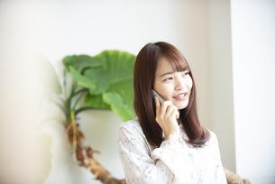 スマホで電話をしている女性の写真素材 [FYI04315664]