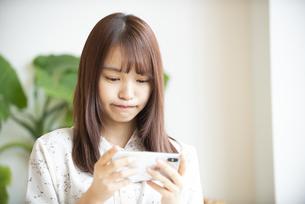 スマホを持っている若い女性の写真素材 [FYI04315668]