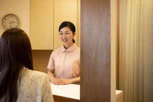 客を見ている笑顔の女性の写真素材 [FYI04315732]