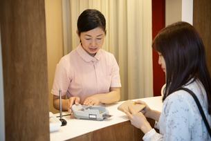 受付で支払いをしている女性の写真素材 [FYI04315735]