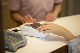 スマホで支払いをしている女性の手元の写真素材 [FYI04315737]