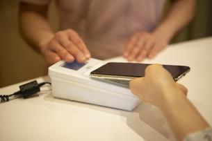 スマホで支払いをしている女性の手元の写真素材 [FYI04315738]