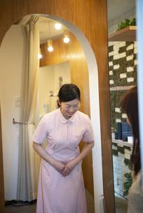 客にお辞儀をして送り出している女性の写真素材 [FYI04315740]