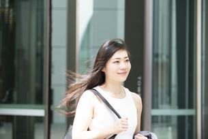 外を歩いているノースリーブ姿の女性の写真素材 [FYI04315761]