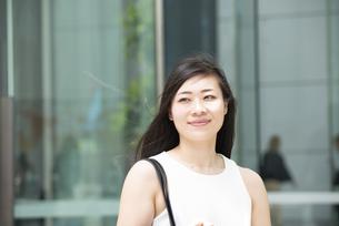 外を歩いているノースリーブ姿の女性の写真素材 [FYI04315763]
