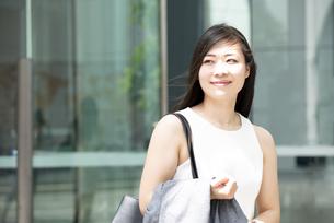 外を歩いているノースリーブ姿の女性の写真素材 [FYI04315764]