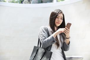 スマホを触っているスーツ姿の女性の写真素材 [FYI04315783]