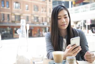 カフェでスマホを見ているスーツ姿の女性の写真素材 [FYI04315792]
