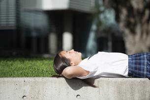 寝っ転がっている制服姿の女子学生の写真素材 [FYI04315824]