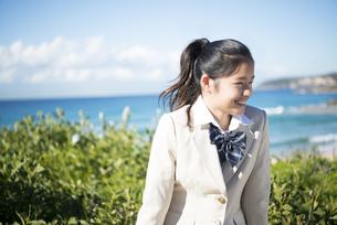 ビーチで笑っている制服姿の女子学生の写真素材 [FYI04315848]