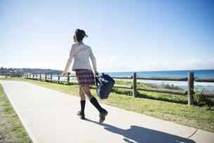 海沿いの道を走っている制服姿の女子学生の写真素材 [FYI04315851]