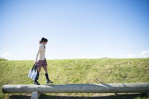 木の上を歩いている制服姿の女子学生の写真素材 [FYI04315853]