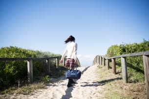 ビーチを歩いている制服姿の女子学生の写真素材 [FYI04315862]