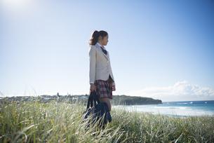 草むらに立っている制服姿の女子学生の写真素材 [FYI04315866]