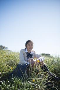 草むらに座っている制服姿の女子学生の写真素材 [FYI04315869]