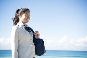 海で笑っている制服姿の女子学生の写真素材 [FYI04315870]