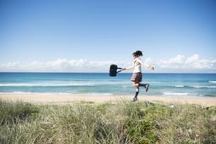 海でジャンプしている制服姿の女子学生の写真素材 [FYI04315871]