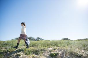 草原を歩いている制服姿の女子学生の写真素材 [FYI04315874]