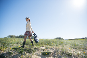 草原を歩いている制服姿の女子学生の写真素材 [FYI04315876]