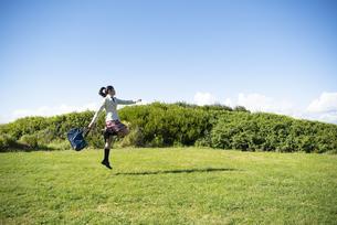草原をスキップしている制服姿の女子学生の写真素材 [FYI04315880]