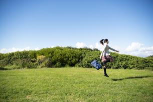 草原をスキップしている制服姿の女子学生の写真素材 [FYI04315881]