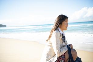 ビーチに座って笑っている制服姿の女子学生の写真素材 [FYI04315889]