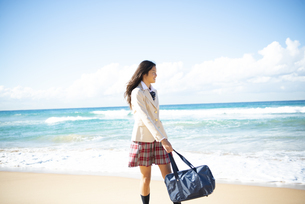 ビーチを歩いている制服姿の女子学生の写真素材 [FYI04315890]