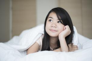 ベッドに横になっている女の子の写真素材 [FYI04315915]